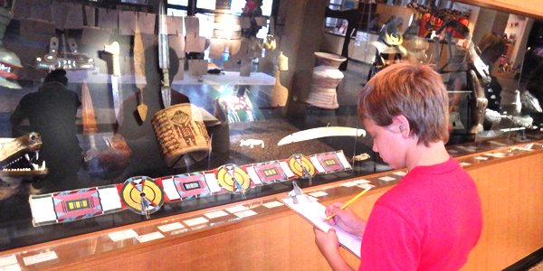 Austin sketching a samurai mask during art day at a Seattle museum